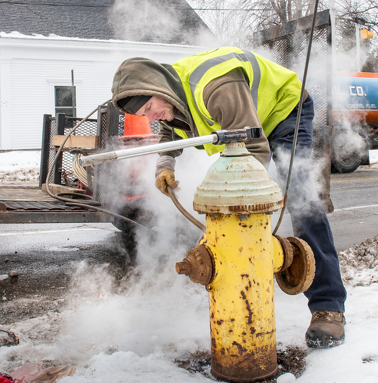 Todd Lester, from Lewiston Water & Sewer Division, removes a steam hose from a frozen fire hydrant at the corner of Frye and College Streets in Lewiston Monday afternoon.  The crews routinely inspect the hydrants throughout the winter to make sure they have not become frozen from a slow leak or after being used by the fire department.  After use the 6 feet of water at the bottom needs to be pumped out.  If they become frozen for any reason, like this one, they can not be used when called upon and there is a possibility of the pipe breaking  when the water freezes.  (Russ Dillingham/Sun Journal)