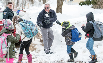 """Norway Detective Gary Hill, center is about to get hit by a snowball as Sierra Powell, blue backpack and pink boots, blocks a giant snowball that he tossed at her while walking home from school on Whitman Street in Norway Thursday afternoon.  Chief Robert Federico, left and the fire chief usually join the group of students from Guy E. Rowe Elementary School every day as they walk to and from school.  """"It's fun and it teaches us to be safe and responsible."""" said Powell.  center, blocks a snowball that (Russ Dillingham/Sun Journal)"""