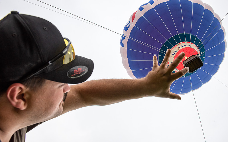 Great Falls Balloon Festival board member Matt Conklin reaches out and pretends to grab the basket of the Re/Max balloon as it does tethered launches Sunday morning after the launch was cancelled.