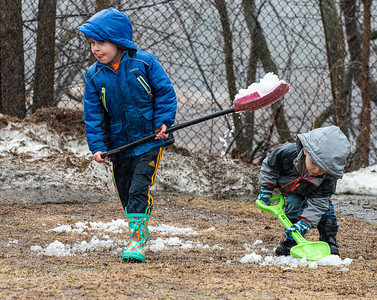 A steady afternoon rain didn't dampen the spirits of brothers Jaden, left, and Sawyer Nolt from shoveling snow from snowbanks around their Lewiston home.  Like many of their neigbors in downtown Lewiston, they were dumping it on the lawn and tar to help it melt.  Their mother was keeping a close watch from a covered porch with an infant in hand yearning to join in.