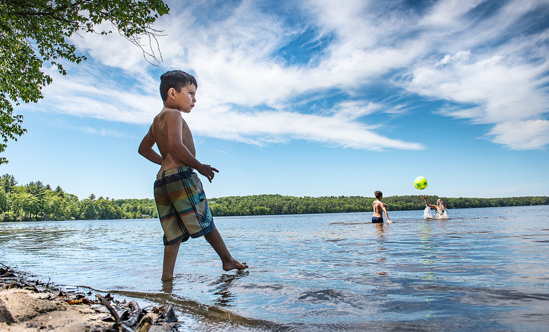 Ethan Townson, 5, is a little hesitant to step into the cold water at Tripp Lake Beach in Poland Thursday afternoon as his friends, Dominic Brunelle, 10 and Kaylee Bickford, 11, play pass with a beach ball.(Russ Dillingham/Sun Journal)