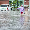 Jessica Morgan sloshes down Maple Street in Lewiston as she makes her way to work Thursday afternoon during a downpour that flooded streets, businesses and houses throughout the area.  (Russ Dillingham/Sun Journal)