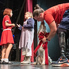 Christy Gardner gets a kiss from Lucky as she ties a bow onto arguably the star of the show before a photo shoot during Monday night's rehersal of Annie at Community Little Theatre in Auburn.