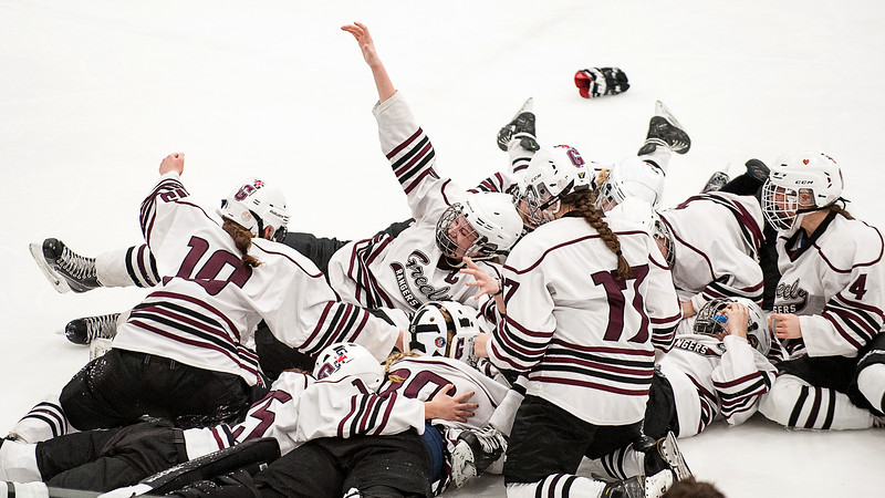 Greely/Gray-New Gloucester's Courtney Sullivan, top with arm raised, celebrates with teammates after their 3-1 victory over Chevrus to win the Girls' Ice Hockey Stae Championship at the Androscoggin Bank Colisee in Lewiston Saturday afternoon. (Russ Dillingham/Sun Journal)