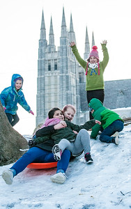 Madyson King, 11, sitting on a sled holds on to her friend, Aylah Valliere, 8 (grey sweatpants) as other friends and siblings cheer and wait for their turn on the one sled they were sharing to slide down a hill in an empty lot off Howe Street in Lewiston, Maine Thursday afternoon January 16, 2019.  The spires of Basilica Saints Peter & Paul rise in the background.  (SUN JOURNAL PHOTO BY RUSS DILLINGHAM)