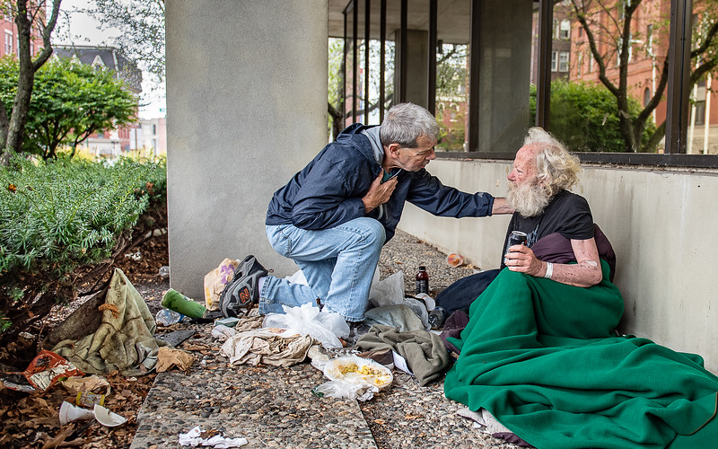 Lewiston resident and longtime RN and homeless advocate, Calvin Dube, left, talks with            in the shadows of a vacant building on Pine Street in Lewiston Wednesday afternoon where he has been living.  When asked what he needed, asked for a tuna sandwich and a sleeping bag.  Dube promised to bring him more blankets and some food.  is looking for a way to get to Florida where he has connections and a better prospect of surviving through the winter.