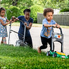 Rachel Frechette helps her mother Samantha mow their lawn in Lewiston Sunday afternoon. Her brother Warren wanted to get in on the action as well and hummed along with his toy mower.