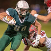 Leavitt's Camden Jordan looks for an opening as he tries to shed Wells' Matt Ouellette during the first half of Saturday night's football game in Turner.