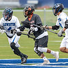 Brunswick's Chandler Coombs, left, gains possession of the ball after bounced around during the opening faceoff of the game where the Dragons slayed the Devils during Wednesday's lacrosse game in Lewiston.  Second from left looking to challenge is Lewiston's Tanner Cortes.