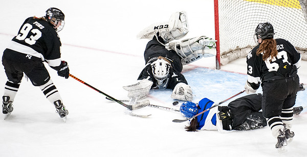 Saint Dominic Academy goalie Payton Winslow dives on the puck before Lewiston's Madison Conley can get a stick on it as she slides through the crease during Monday night's hockey game at the Androscoggin Bank Colisee in Lewiston.  (Russ Dillingham/Sun Journal)