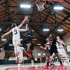 Bates College's James Mortimer, left swats at the running floater Thomas' Demetris Webster put up as he drives to the basket during the first half of Tuesday's basketball game in Lewiston. (SUN JOURNAL PHOTO BY RUSS DILLINGHAM)