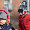 Max Frechette patiently waits on the sidewalk of Main Street in Farmington Saturday morning December 7, 2019 while waiting with family and friends for the Chester Greenwood Day Parade to march past.  His friend, Reid McCarthy, background, raced up and down a driveway with other kids from Farmington who's families came down to watch the parade.