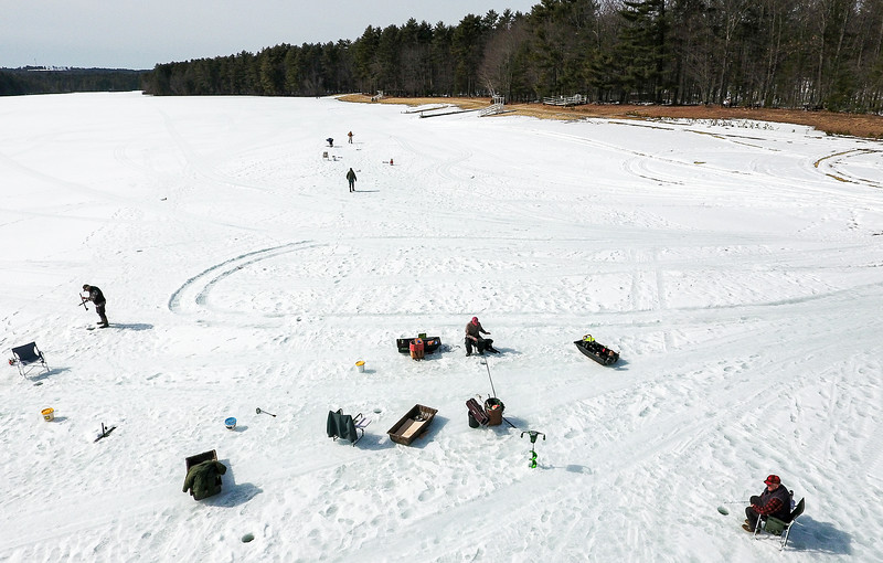 "Dave Flynn, of Lyman, bottom right, and several of his friends stretch out the ice fishing season on Range Pond in Poland Tuesday afternoon.  ""It's better than sitting on the couch and is a whole lot of fun, especially when they are biting."" said Flynn.  With about 18 inches of ice left, Range Pond is one of the few safe places left in the area to fish.  To watch an aerial video of the area, visit sunjournal.com.  (Russ Dillingham/Sun Journal)"