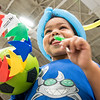 Malikye Harrison, 3 of Lewiston takes a taste of a lollypop he just got while trying to manage a handful of giveaways from Tuesday night's National Night out celebration that was moved inside at the Colisee after a fast moving storm swept through town.(Russ Dillingham/Sun Journal)