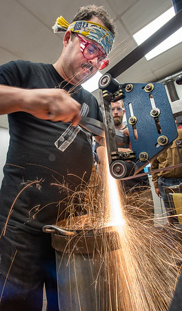 )ne of the most famous and well known swords is that of ancient Rome, the Gladius.  Sam Salvati, a well known blacksmith from Maryland demonstrates techniques on grinding down the edge to his students. Their solid block of metal they started with at the beginning of the week are starting to take shape during their week long Forged Gladius class at New England School of Metalwork in Auburn Wednesday afternoon. The world famous school has ongoing classes throughout the year.  For more information on upcoming classes and workshops visit http://www.newenglandschoolofmetalwork.com/