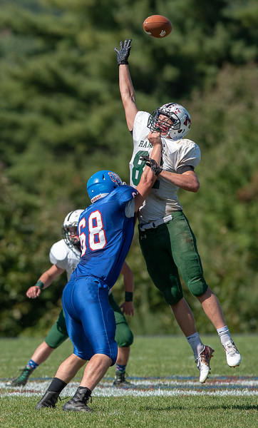 Despite being blocked by Oak Hill's Alex Fournier, left, Winthrop-Monmouth-Hall-Dale's Jevin Smith managed to tip a pass and force an incomplete pass during Saturday afternoon's football game in Wales.
