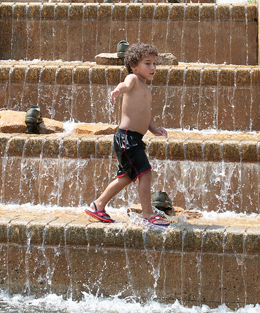 Mlik Mohamud, of Lewiston, walks across the water fountain at Festival Plaza in Auburn Sunday afternoon while trying to stay cool with his siblings and father.