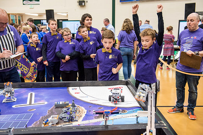 Jayce Thompson raises his hands in victory as his his robot completes a task during the Western Maine FIRST Lego League Qualifier at Spruce Mountain High School in Jay, Maine on Saturday November 17, 2018 as members of his team from RSU 16 in Poland, The Enforcers, react. (Russ Dillingham/Sun Journal)