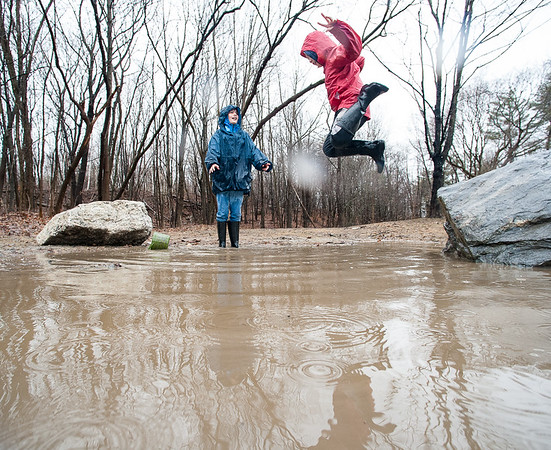 """After an unspecified amount of time, Myles Dubois, 8 gets to jump back into a giant puddle in Sunny Side Park in Lewiston Tuesday afternoon while playing a game of """"Puddles is Lava"""" with his sister Alexis, 11, background, across the street from their home on Winter Street during another day of soakig rain.  (Russ Dillingham/Sun Journal)"""