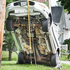 Donella Ssekiziyivu looks up at the car she was a passenger in after she jumped from when it came to rest on a guy-wire on a utility pole at the corner of Pleasant and Bartlett Streets in Lewiston Monday afternoon.  She said her friend who was driving had a seizure and lost control of the car. (Russ Dillingham/Sun Journal)