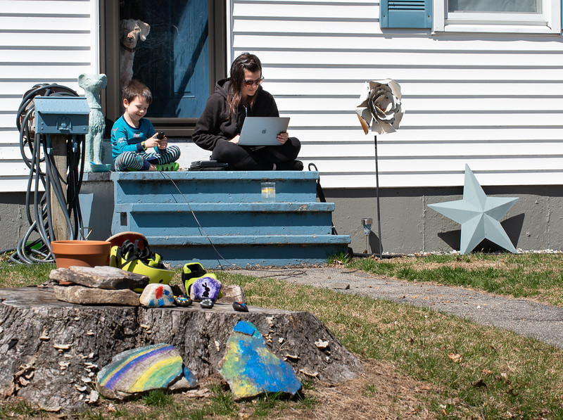 Lyndsay Blais and her son Ryder soak up the afternoon sun as they do work and play games on their front steps in Lisbon Wednesday afternoon.