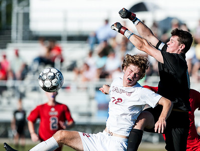 Gray New Gloucester goalie Brannon Gilbert punches the ball away on a corner kick as he colides with Cape Elizabeth's Nick Clifford during the first half of Saturday's soccer match.  (Russ Dillingham/Sun Journal)