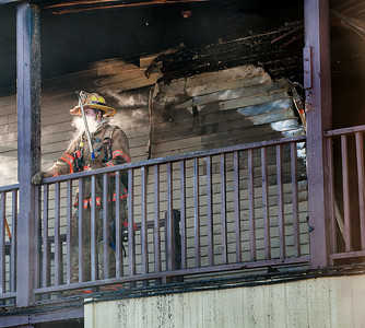 A Lewiston firefighter catches his breath after coming out of an apartment on the second floor Wednesday morning at 906 Lisbon Street in Lewiston. (Russ Dillingham/Sun Journal)