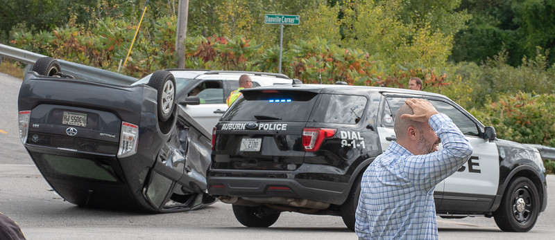 Jason St. Onge, of Lewiston, rubs the back of his head after hitting it on the roof of his SUV when it flipped over Tuesday afternoon on Washington Street in Auburn. He said he drove down Danville Corner and was cutting across Washington Street to Beech Hill Road and did not see a small blue sedan traveling North on Washington Street, pulling out into her path.  The woman, who has not been identified, walked away and was being evaluated by rescue personel.