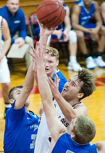 Bates' James Mortimer drives to the basket and floats one in between UNE's Ryan Matthews, left and Jackson McCoy during the first half of Sunday night's basketball game in Lewiston. (Russ Dillingham/Sun Journal)