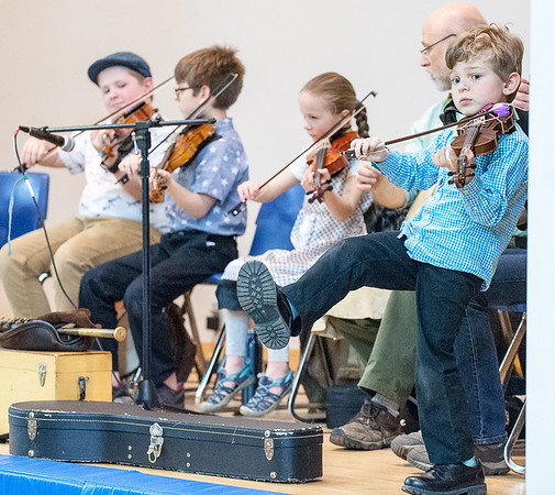 The youngest member of the Maine Folque Co-op, Elliott Gilg, 5, right, joins other members of the group on the stage at Turner Primary School Thursday afternoon during a music and dance program that some of the schools students took part in. Some of the others in the group are from left to right in the background are, Owen Kennedy (fiddler & bodhran player, age 12), Alden Gilg (fiddler, 10), Una Shostak (fiddler, age 8) & Anthony Shostak from the Turner Library, who helped fund and coordinated the event. (Russ Dillingham/Sun Journal)