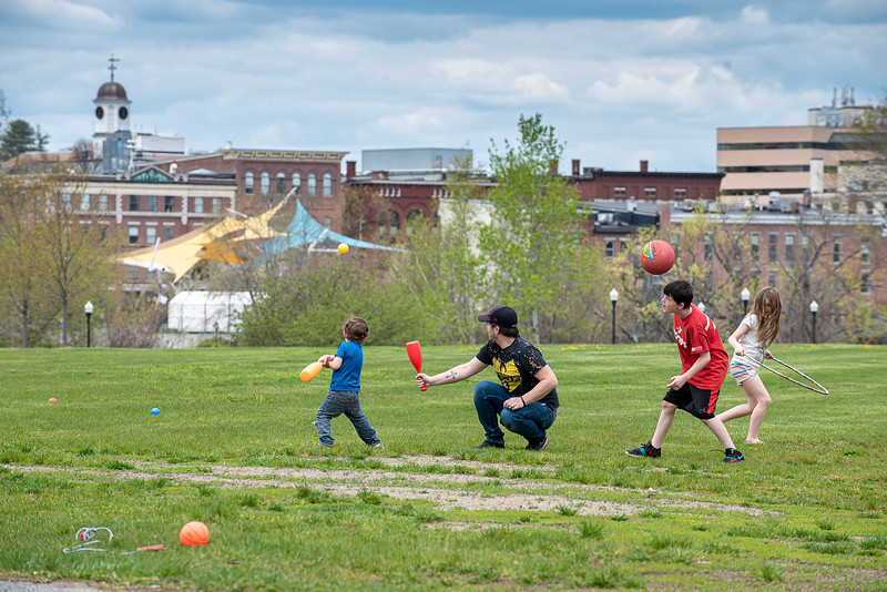 Nathan Kelley, center, watches the ball fly off his makeshift tee that his stepson, Kayden McWilliams hit from while playing in Simard Payne Memorial Park in Lewiston Sunday afternoon.  At right are his other two children, Madison McWilliams, right and Connor Landry, second from right.