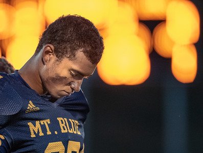 Mt. Blue football captain Kevon Johnson bows his head during a moment of silence to honor the victims of Monday's tragic explosion in Farmington prior to kickoff of Friday night's football game against Brewer in Farmington.