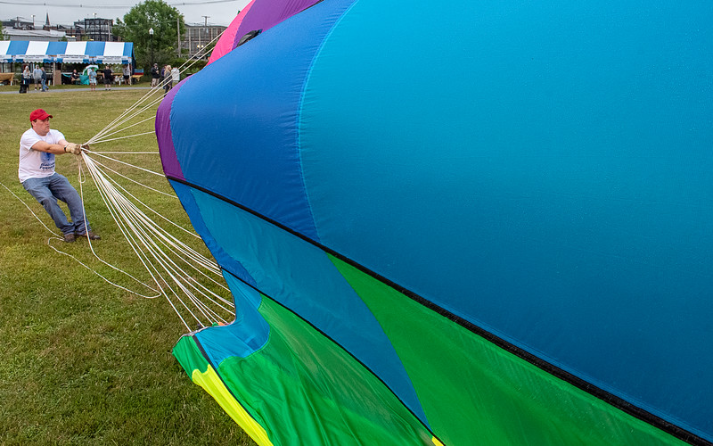 Nick Bouyea, of Lewiston, a crew member for the balloon Neon Dreamz holds onto the crown lines as it deflates at Simard-Payne Memorial Park in Lewiston Saturday morning during the Great Falls Balloon Festival.  Two balloons inflated but were taken down quickly as a light rain grounded the 3rd scheduled launch in a row at the start of the 2019 festival that continues through Sunday with morning and evening launches at 6:00.
