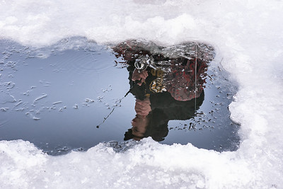 After his 2 year old son got cold and had enough ice fishing for the day, Matthew Hunt,  joined his friends gigging in a hole they made with their ice augers on Halls Pond in Paris Sunday afternoon, December 8, 2019 as they wait for a flag to pop up on traps they set all around the lake. Marshall is reflected in the water as lines of Nick Parent, of Biddeford, Maine and Tony Sargent, right, of Turner, Maine join his.