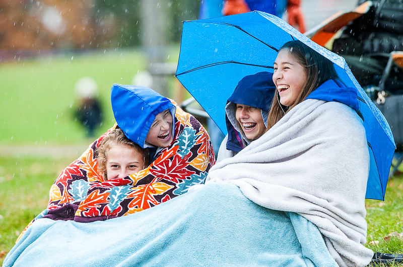 Oak Hill High School students, from left to right, Emily Dillman, Brianna Dumais, Lexi Finn and Madison Drew have a laugh as they try to keep dry and warm during Saturday's Class D South quarterfinal playoff game between their Oak Hill Raiders and the Lisbon Greyhounds during a constant rain/snow mix in Lisbon, Maine Saturday afternoon October 27, 2018. (Russ Dillingham/Sun Journal)