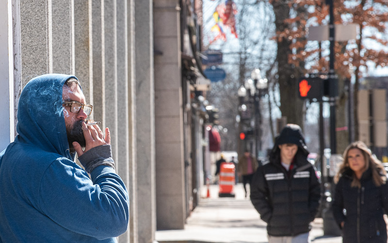 "Benjamin Shapleigh-Archer, of Lewiston, enjoys a cigarette on Lisbon Street before having his lunch at the Lewiston Public Library Thursday afternoon.  ""I don't think it's right and is unfair."" he said about the no smoking ban on Lisbon Street."