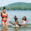 Lanyha Spearman, left, splashes water for her dog Lily to jump after as Na'Kaiyah Sevey, 5, screams in delight. The cousins came to Sabattus Pond in Sabattus Wednesday afternoon to cool off on one of the hottest days of the year. (Russ Dillingham/Sun Journal)