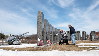 Joe Derocher, from Lewiston Maine, a combat engineer who served in Vietnam, holds his service dog Cooper at Veterans Memorial Park in Lewiston Thursday morning, March 29, 2018 as he points to his father's name engraved on one of the memorial stones at Veterans Memorial Park in Lewiston following a brief ceremony honoring Veitnam Veterans.  Derocher was telling Laurence Parks, right, of Sabattus, also a Vietnam veteran who served aboard an aircraft carrier about his father who landed on Omaha beach on D-day in WWII and was severly wounded in the Battle of the Bulge.  (Russ Dillingham/Sun Journal)