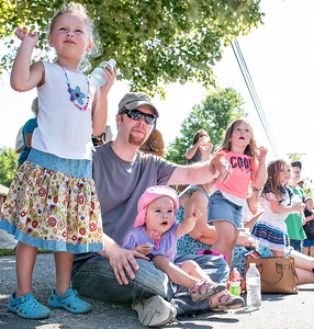 Alice Lamp, sitting between the legs of her father Devon, points to a horse coming down the street during the annual Labor Day Parade in Buckfield as sister Elsie waves Monday morning.  (Russ Dillingham/Sun Journal)