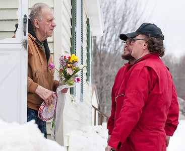 "Gilman Dube, left, is stunned and surprised as he stands in his doorway of his Auburn home Wednesday morning.  Murray-Heutz Oil delivery drivers Roger Pelletier, right and Brandin Daigneault, background, explain to him that they were there to ""top off"" his oil tank and deliver the flowers and candy as part of their program called ""Fuel Your Love""  This is the third year of the program that delivered nearly 2,000 gallons of free fuel to 9 different customers throughout the Central Maine area.   (Russ Dillingham/Sun Journal)"