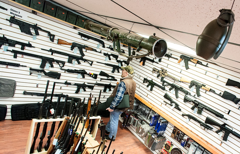 """Bill O'Neill, of Rumford, eyes an AR-15 he was considering purchasing at G3 Firearms in Turner Thursday afternoon.  """"I used to have a bunch of them, but sold those for long range ones that I use for target shooting but am thinking about buying an AR."""" said O'Neill.  (Russ Dillingham/Sun Journal)"""