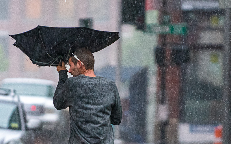 A man has his umbrella turned inside out by a gust of wind as he battles a driving rain walking down Pine Street in Lewiston Wednesday night.