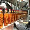 Inspector Irene Warner checks Fireball wiskey bottles on the line at Boston Brands of Maine in Lewiston Wednesday.