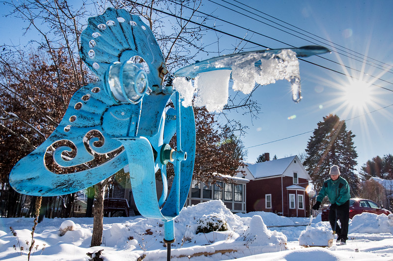 "Dennis Connelly uses a snow scoop to clear his driveway Thursday morning January 3, 2019, on Gill Street in Auburn, Maine. ""I would much rather be working in the garden but this is what you get when you live in Maine. At least this snow is light, unlike the last storm.""The blue whirligig in the foreground is one of many in his snow-covered garden. (Sun Journal photo by Russ Dillingham)"