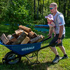 Lisbon Police Officer Chris Miller hauls a load of wood to the woodshed at the home of Karl and Tammy Dostie in Sabattus Wednesday morning.