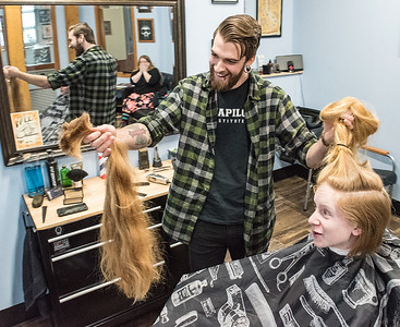 Jen August, reflected in mirror and her son, Michael Hynes, 14, of Auburn, react as barber Rick Morrow shows off Michael's hair that he just cut off at Apollo Barbers in Auburn Saturday morning.  Hynes has only cut his hair 3 times in his life and decided he wanted a change and to try something different.  He wants to donate it to a non profit with a worthy cause but has not yet decided where. (Russ Dillingham/Sun Journal)