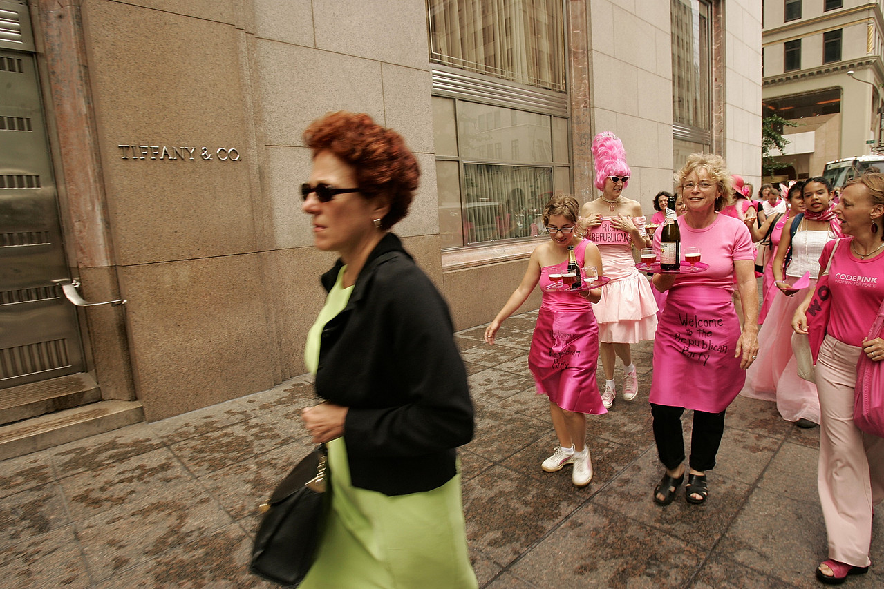 "8/30/2004 -- New York, NY -- Protesting the RNC in NYC -- Members of the activist organization CODEPINK march down past Tiffany & Co in Manhattan on their way to the Regency hotel for a demonstration. The group was divided roughly in half, with one contingent representing the ""rich Republicans"" demanding champagne and hors-de-vours service from the other contingent, who represented ""poor people."" CODEPINK is a women-initiated peace and social justice movement that demonstrates in creative and non-violent ways -- and always in pink. Photo by Dina Rudick, The Boston Globe."