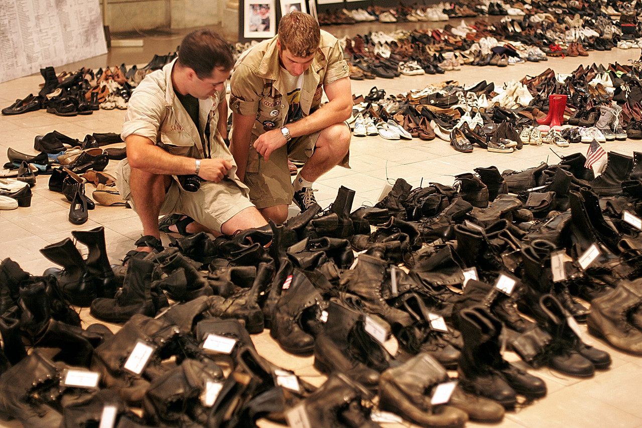 "8/31/2004 -- New York,  NY -- 55 Washington Square South -- Eyes Wide Open exhibit -- Judson Memorial Church -- Rob Sarra (left) and Tim Goodrich, both veterans of Operation Iraqi Freedom, shed tears as they adjust an American flag on the boots labled with the name of  a fallen comrade, Sgt. Kirk Allen Straseskie, whom Sarra called ""Ski"" for short.  ""Ski"" was a Wisconsin native, and drowned in Iraq while trying to save his fellow soldiers when their helicopter crashed in the river. Sarra has tattooed Ski's name and number on his upper arm. Sarra and Goodrich were viewing an exhibit called ""Eyes Wide Open,"" which displayed 975 pairs of militarty boots (the current number of US soldiers KIA) and hundreds of civillian shoes to represent those killed in the war. Photo by Dina Rudick, The Boston Globe."