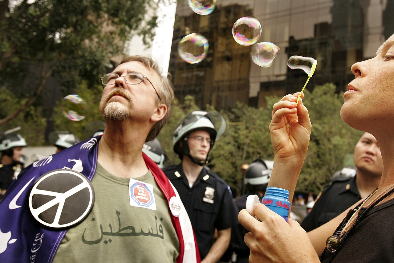 "8/30/2004 -- New York, NY -- Near United Nations on 1st Avenue and 47th Street -- Amanda Martin, an activist from Columbia, SC with the Carolina Peace Resource Center, blows bubbles as she and Arnold Karr (left; also from SC and the CPRC) stand in an evening rally near the United Nations in Manhattan on Monday, August 31, 2004. Amanda said: ""I'm blowing bubbles because they're a sign of peace and hope. They're made of soap...and of water. It's time to scrub this country clean."" Monday was the first day of the Republican National Convention. Photo by Dina Rudick, The Boston Globe."