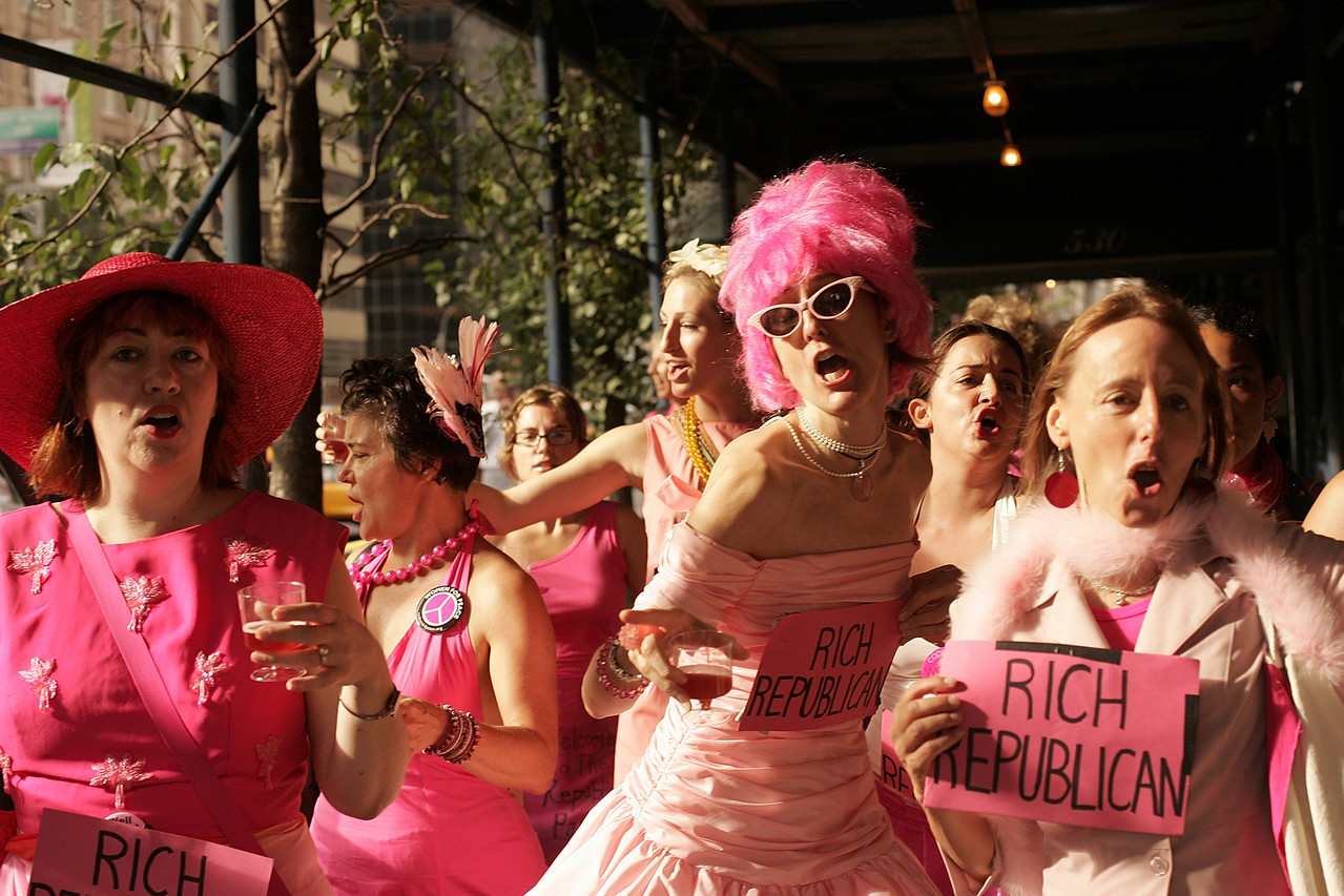 """8/30/2004 -- New York, NY -- Protesting the RNC in NYC -- Members of the activist organization CODEPINK march down Park Avenue in Manhattan on their way to the Regency hotel for a demonstration. The group was divided roughly in half, with one contingent representing the """"rich Republicans"""" demanding champagne and hors-de-vours service from the other contingent, who represented """"poor people."""" CODEPINK is a women-initiated peace and social justice movement that demonstrates in creative and non-violent ways -- and always in pink. Photo by Dina Rudick, The Boston Globe."""